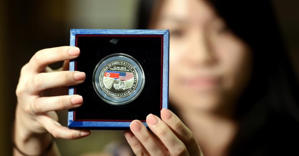 11.jun.2018 - Funcionária exibe uma amostra do medalhão apresentado pela Casa da Moeda de Singapura para comemorar a cúpula entre o presidente dos EUA, Donald Trump, e o líder da Coreia do Norte, Kim Jong Un