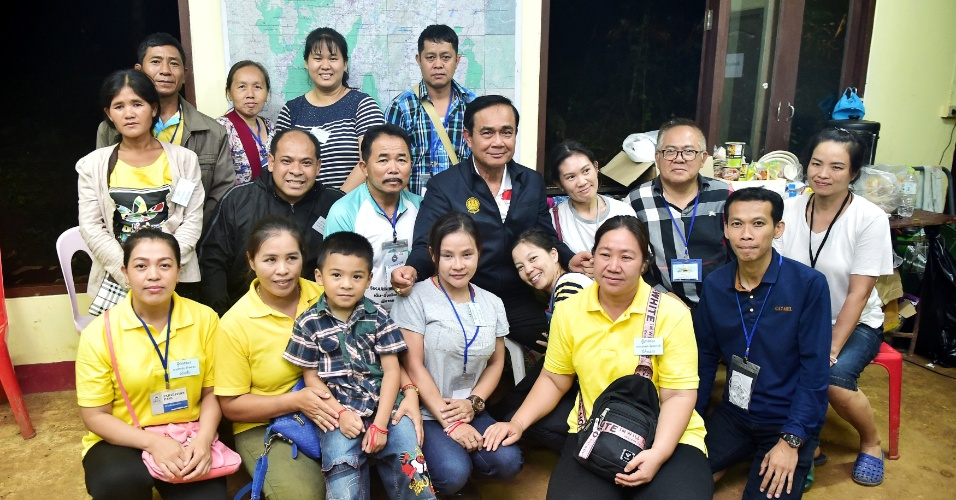 9.jul.2018 - O primeiro-ministro da Tailândia, Prayuth Chan-ocha, posa com parentes de meninos presos na caverna inundada no complexo de Tham Luang em Chiang Rai