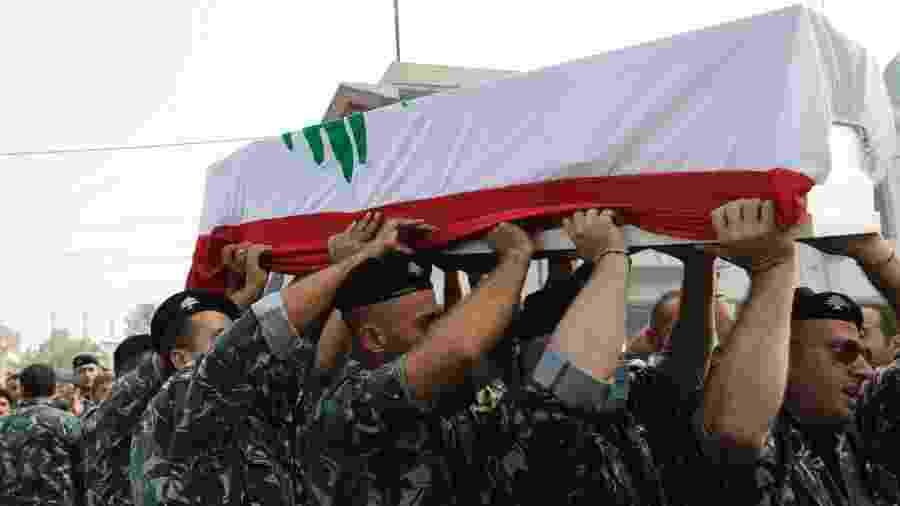 Bombeiros carregam o caixão de homem morto na explosão do Porto de Beirute - ANWAR AMRO/AFP