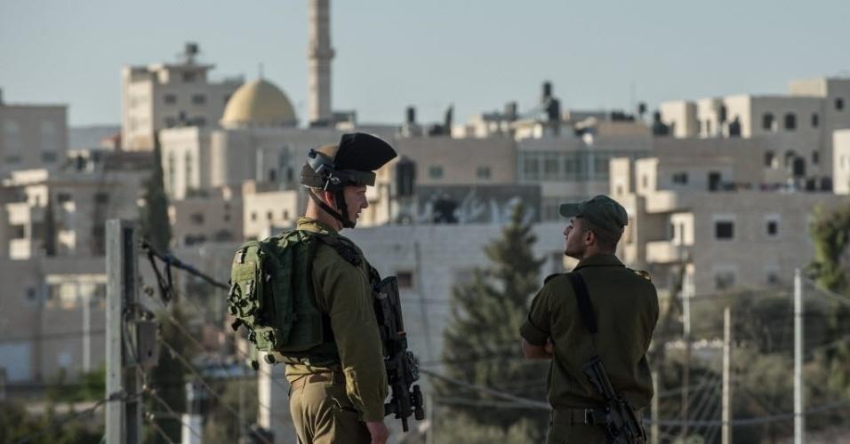 21.out.2015 - Membros das forças de segurança israelenses ficam de guarda no local onde um ataque foi registrado na estrada 60, rodovia principal que leva do norte ao sul da Cisjordânia. Uma palestina ficou ferida ao ser alvejada por soldados israelenses quando supostamente se aproximou com uma faca de um assentamento judaico. Nesta terça-feira (20), aconteceram outros três episódios de tentativas e ataques com facas de palestinos contra israelenses, nos quais os quatro agressores morreram