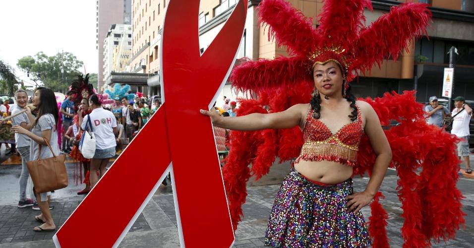 1º.dez.2015 - Transgênero segura o laço vermelho, símbolo da luta contra o vírus HIV, durante parada pelo Dia Mundial de Luta contra a Aids, em Manila, Filipinas