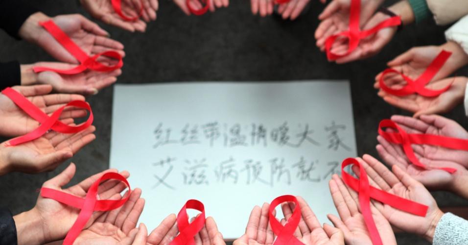 """1º.dez.2015 - Voluntários seguram fitas vermelhas com o símbolo da luta contra o HIV/Aids próximo de cartaz  em evento para o Dia Mundial de Luta contra a Aids em Chongqing, na China. No cartaz, em chinês, lê-se: """"As fitas vermelhas trazer o calor a todos para prevenir a Aids"""""""