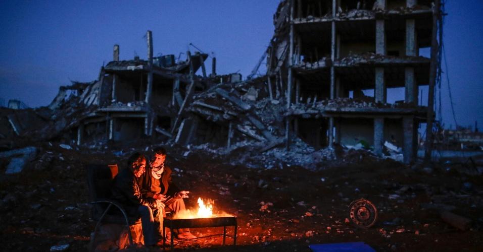 22.mar.2015 - Homens curdos sentam junto a uma fogueira perto de edifício destruído, na cidade curda de Kobane, também conhecida como Ain al-Arab, na Síria
