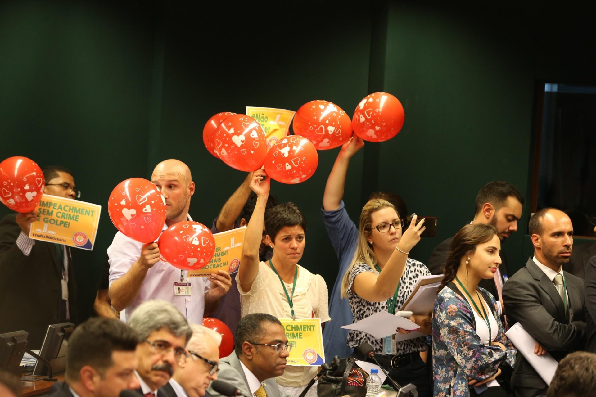 04.abr.2016 - Manifestantes pró-governo agitam balões vermelhos e exibem cartazes enquanto o advogado-geral da União, José Eduardo Cardozo, apresenta a defesa da presidente Dilma Rousseff à comissão especial que avalia o pedido de impeachment da mandatária na Câmara dos Deputados, em Brasília
