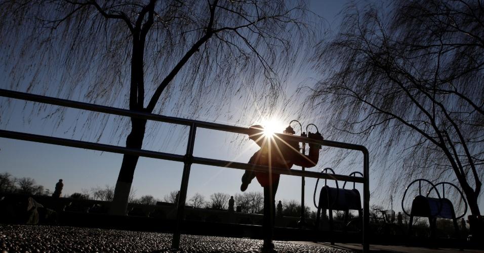 22.dez.2016 - Mulher faz exercícios em parque com o céu azul depois de dias com níveis perigosamente altos de poluição do ar em Pequim, na China