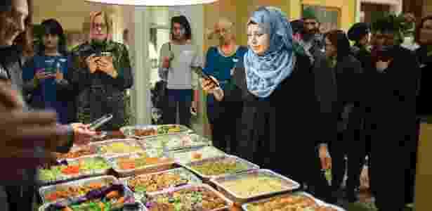 Dyana Aljizawi fotografa a comida que ela preparou para convidados do Clube de Jantar da Síria - Tess Mayers/The New York Times