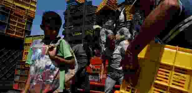 """Menino observa cesta de frutas enquanto o caminhão de Humberto Aguilar"""" é carregado  - Carlos Garcia Rawlins/Reuters"""