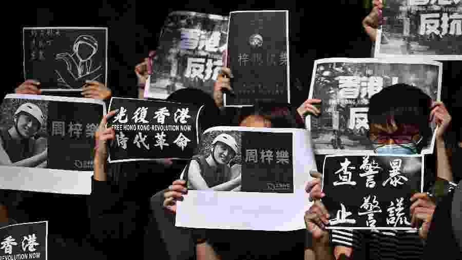 Estudantes da Universidade de Ciência e Tecnologia de Hong Kong participam de uma marcha após a morte do estudante Alex Chow, 22, após confrontos entre policiais e manifestantes. - Philip FONG / AFP