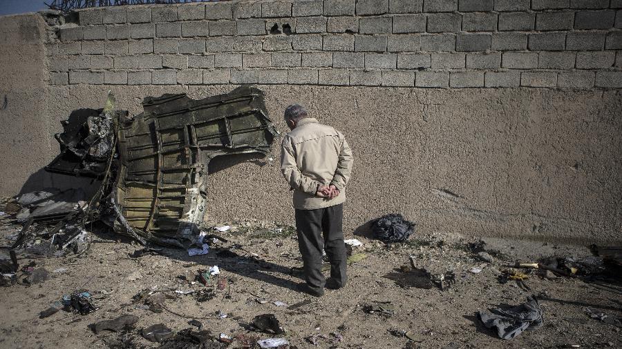 Homem observa parte do avião ucraniano Boeing 737, que caiu em Teerã, no Irã, pouco após decolar - Xinhua/Ahmad Halabisaz