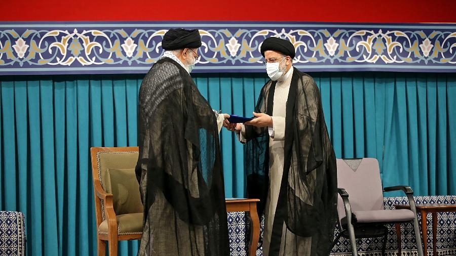 3.ago.2021 - O líder supremo do Irã, aiatolá Ali Khamenei, durante a cerimônia de posse de Ebrahim Rais (direita) - AFP/HO/Khamenei.IR
