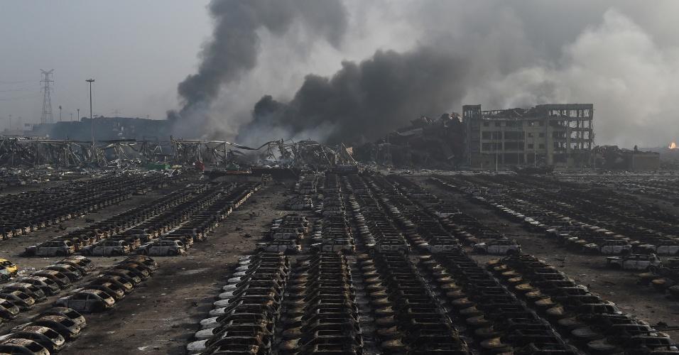 13.ago.2015 - Coluna de fumaça por trás de fileiras de carros queimados no local de uma série de explosões em um armazém em Tianjin, na China