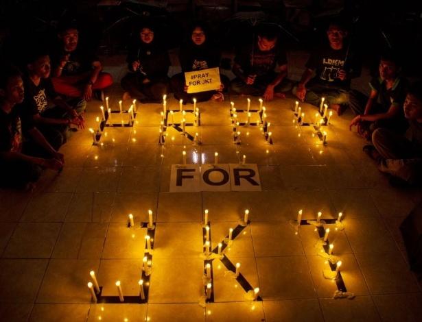 """14.jan.2016 - Grupo de estudantes indonésios protestam à luz de velas em Surabaya, na ilha de Java, contra os ataques a bomba que abalaram Jacarta. As  velas formam a frase """"Pray for JKT"""" (""""Rezem por Jacarta""""). Uma série de explosões e um tiroteio deixou ao menos sete mortos na capital indonésia. O Estado Islâmico assumiu a autoria dos ataques"""