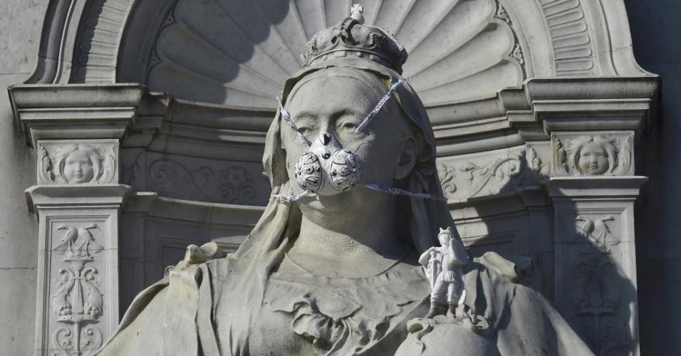 18.abr.2016 - Os ambientalistas do Greenpeace colocaram uma máscara na estátua de rainha Victoria, em frente ao palácio de Buckingham Palace, para protestar contra a poluição do ar em Londres
