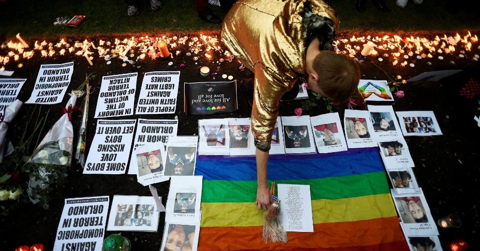 13.jun.2016 - Rapaz coloca uma boneca em cima da bandeira do movimento LGBT (Lésbicas, Gays, Bissexuais, Travestis, Transexuais e Transgêneros) em Londres, no Reino Unido. Esta é mais uma das homenagens às vítimas do tiroteio da boate Pulse que ocorreu na madrugada de domingo em Orlando, nos Estados Unidos. O atirador foi identificado como Omar Mateen, um cidadão americano que estava no radar do FBI desde 2013