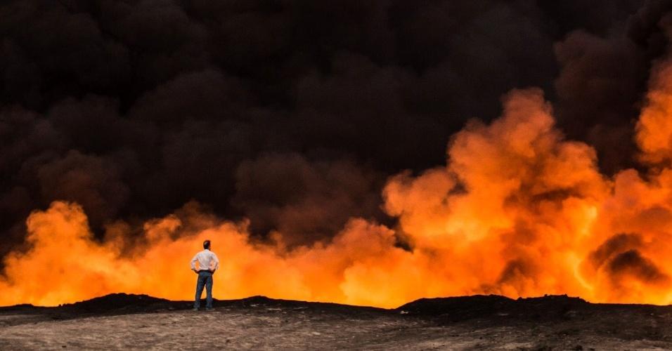20.out.2016 - Homem observa campo de petróleo em chamas em Qayyarah, a 60 km de Mossul. O Exército iraquiano tenta retomar a cidade de 1,5 milhão de habitantes considerada bastião do Estado Islâmico