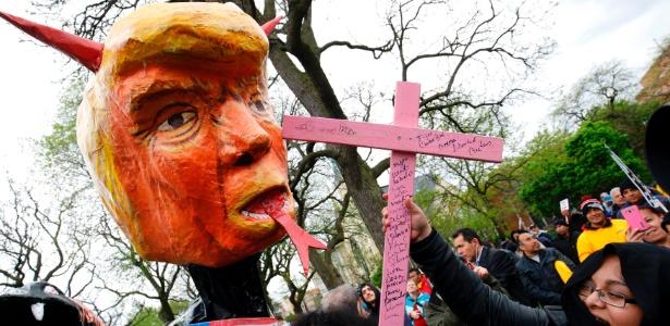 Manifestante atinge cabeça do presidente Donald Trump feita em papel machê em protesto do 1º de maio em Chicago