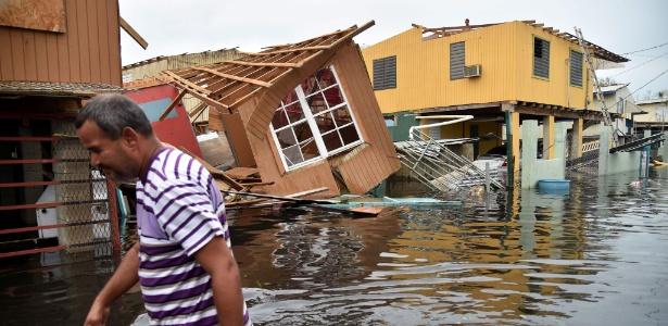 Homem passa em frente a uma casa inundada e destruída pelo furacão Maria em Cataño, em Porto Rico