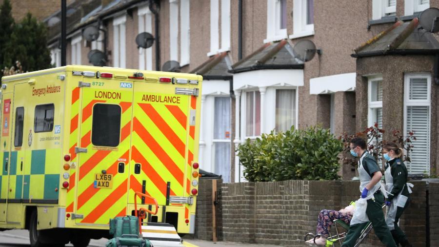 30.mar.2020 - Paramédicos usando máscaras contra coronavírus levam paciente para ambulância em Londres - Hannah McKay/Reuters