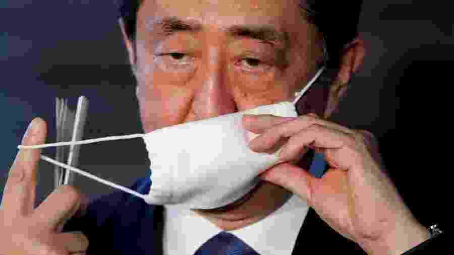 Primeiro-ministro do Japão, Shinzo Abe, tira máscara de proteção ao chegar para pronunciamento em Tóquio -