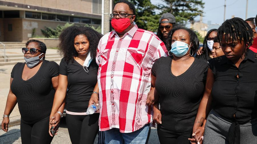 25.ago.2020 - Familiares de Jacob Blake, que foi baleado por policiais diante dos filhos, caminham de mãos dadas em protesto contra a ação policial - Kamil Krzaczynski/AFP