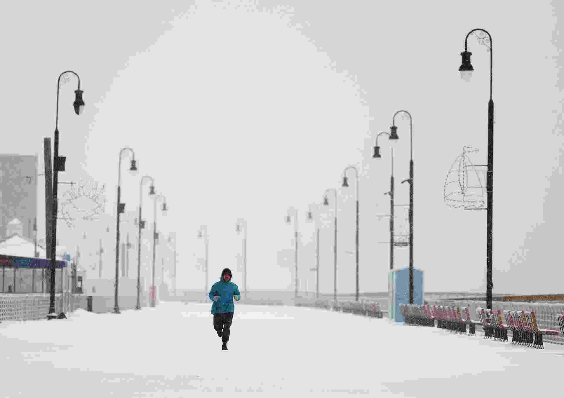 17.dez.2020 - Homem corre em Long Beach, Nova York; é a primeira grande tempestade de neve da temporada nos EUA - AL BELLO/AFP