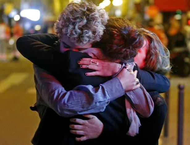 14.nov.2015 - Pessoas se abraçam em rua próxima à sala de concertos Bataclan, após série de ataques terroristas em Paris