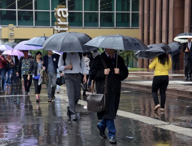 Pedestres se protegem da chuva e do frio na Avenida Paulista, em São Paulo (SP), na tarde desta terça-feira (1)