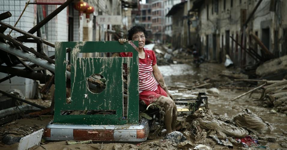 11.jul.2016 - Suja de lama, mulher se senta entre escombros após a passagem do tufão Nepartak no condado de Minqing, província de Fujian, na China. Mais de 200 mil pessoas tiveram que ser realojadas por causa da tempestade
