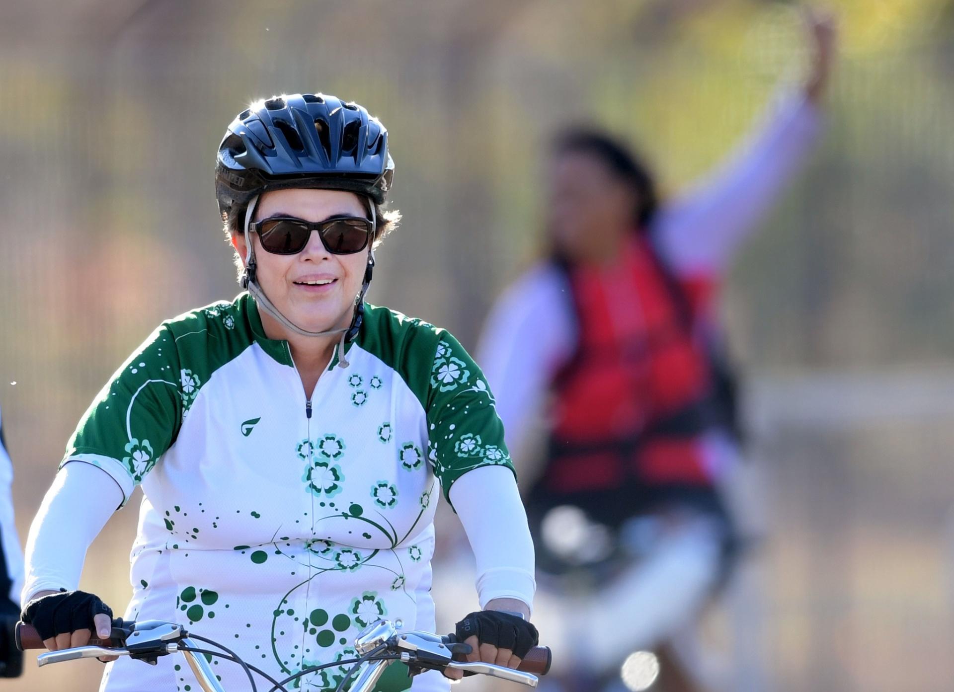28.ago.2016 - A presidente afastada, Dilma Rousseff, anda de bicicleta nos arredores do Palácio do Alvorada, em Brasília, na véspera de seu depoimento no Senado que julga o impeachment de seu mandato