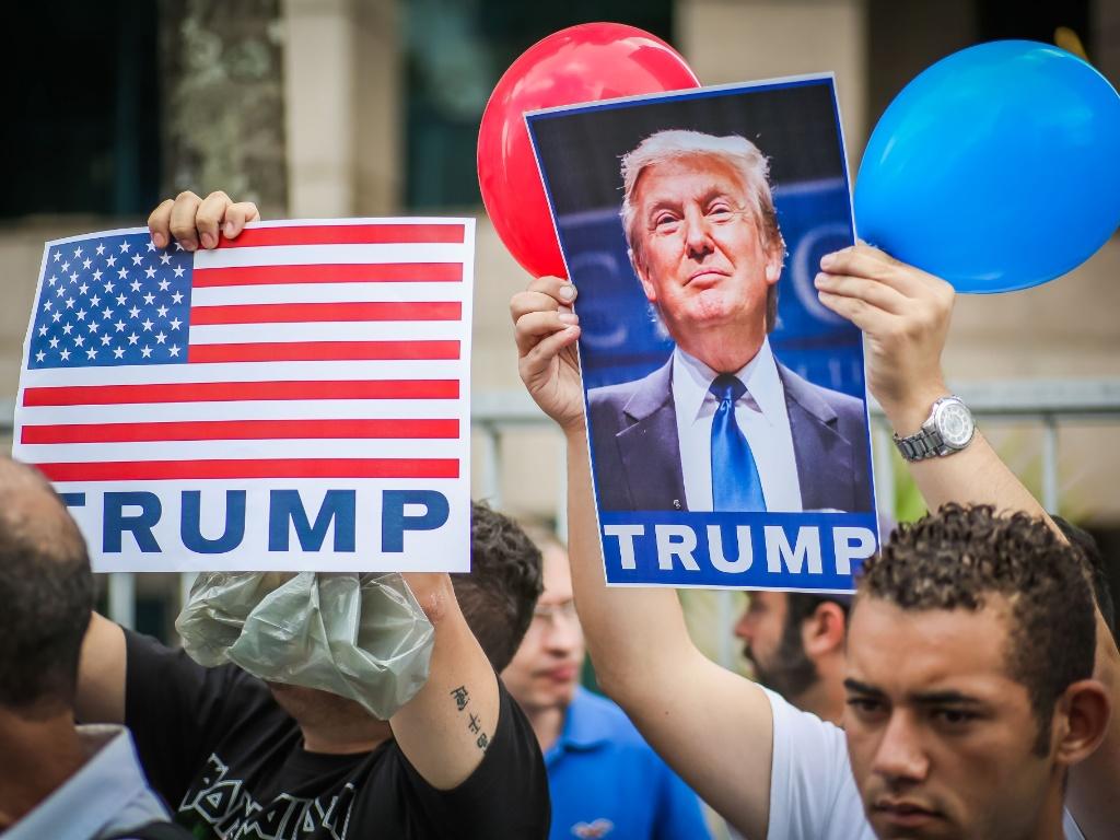 """29.out.2016 - Cerca de 20 manifestantes se encontraram na av. Paulista, em São Paulo, para participar de um ato pró-Trump. Os manifestantes, muitos dos quais vestiam camisetas do deputado Jair Bolsonaro, levavam cartazes com dizeres como """"Hillary is the American Dilma"""" (Hillary é a Dilma americana) e """"Obama and Hillary created Isis"""" (Obama e HIllary criaram o Estado Islâmico, uma das frases ditas por Trump)"""