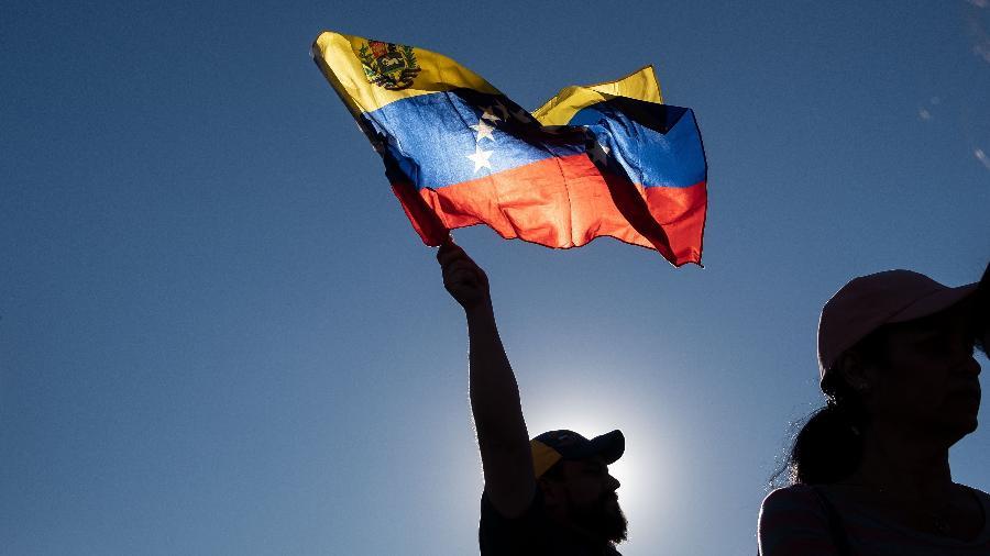 Manifestantes erguem as mãos durante protesto contra o presidente Nicolás Maduro, onde o presidente da Assembleia Nacional se autodeclarou presidente da Venezuela - Guillermo Arias/AFP