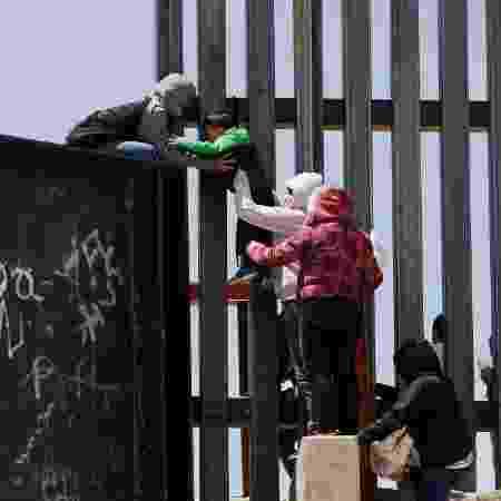 22.jun.2019 - Migrantes pulam sobre muro para cruzar a fronteira dos EUA com o México em Ciudad Juarez - Jose Luis Gonzalez/Reuters