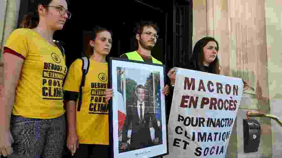 Ativistas do clima seguram uma foto do presidente francês Emmanuel Macron em frente à prefeitura de Saint-Ouen - Dominique Faget/AFP