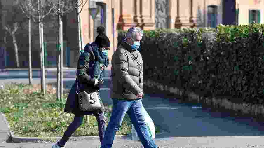 22.fev.2020 - Homem e mulher usando máscaras andam na rua em Codogno, na Itália - Flavio Lo Scalzo/Reuters