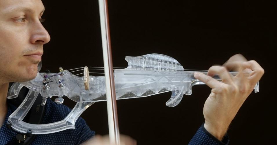 """11.set.2015 - O engenheiro e violinista profissional Laurent Bernadac toca o """"3Dvarius"""", um violino cujo corpo foi feito em uma impressora 3D com resina transparente, em Paris, na França"""