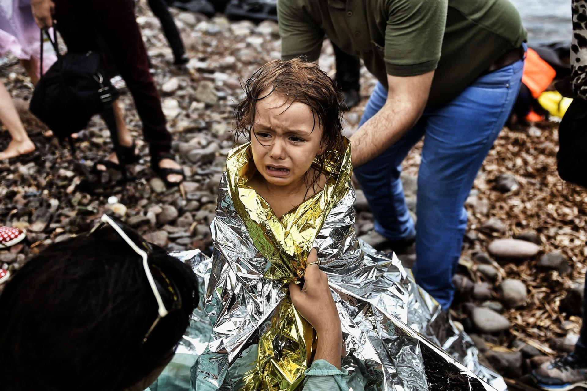 28.set.2015 - Garota síria é recebida com cobertor térmico na chegada à ilha grega de Lesbos. Ela estava com um grupo de imigrantes que cruzou o mar Egeu. Uma embarcação com refugiados afundou e deixou dezenas de mortos