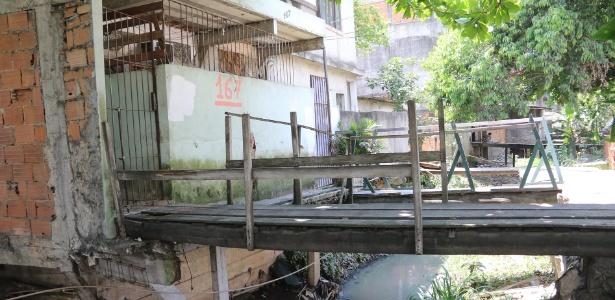 Pontes de madeira sobre o esgoto ligam casa à rua na favela Vila União Curicica, no Rio