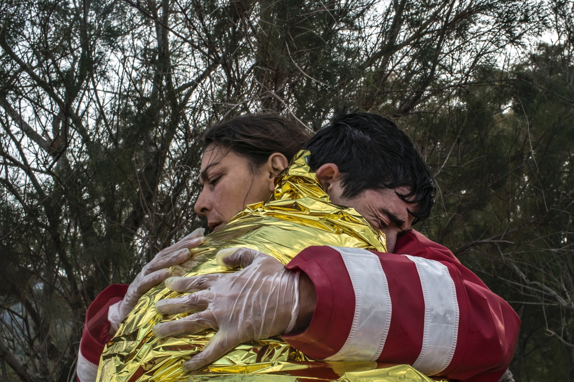31.out.2015 - Embrulhado em manta térmica, refugiado afegão chora ao receber atendimento médico de uma funcionária da Cruz Vermelha em praia da Ilha de Lesbos (Grécia)