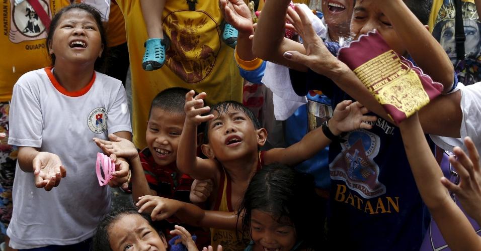 7.jan.2016 - Crianças esperam para receberem água benta durante serviço religioso realizado dois dias antes da procissão anual do Nazareno Negro, em Manila (Filipinas)