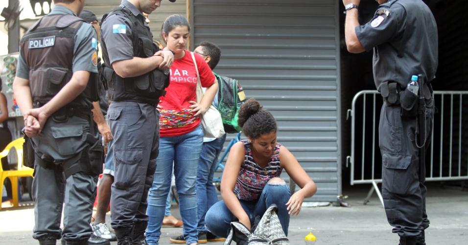 7.set.2016 - Policiais militares revistam mochila de mulher na avenida Presidente Vargas, no centro do Rio de Janeiro, nesta quarta-feira, onde acontece o desfile de 7 de setembro e protestos contra o governo Temer