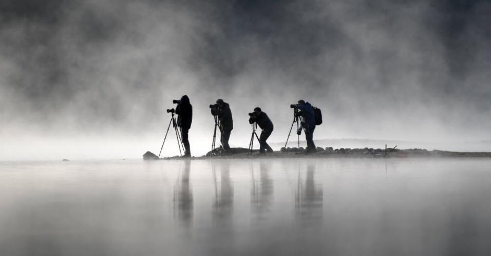 28.nov.2016 - Névoa envolve fotógrafos no lago Qishu, em Huangshan, na China