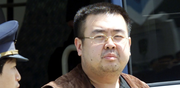 Foto de maio de 2001 mostra Kim Jong-nam (dir.) sendo escoltado por um agente de imigração no aeroporto de Narita, próximo a Tóquio, no Japão