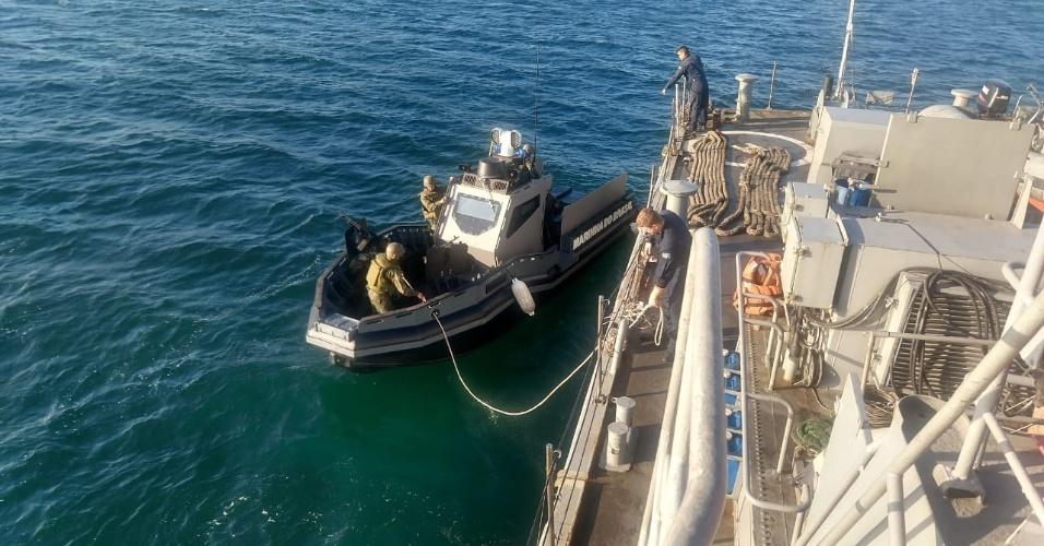 Militares lançam bote de patrulha a partir de fragata para patrulhar praia do Leme e costa da Urca