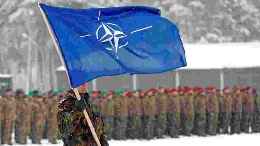 Militar carrega bandeira da Otan em cerimônia militar em base na Lituânia - REUTERS/Ints Kalnins
