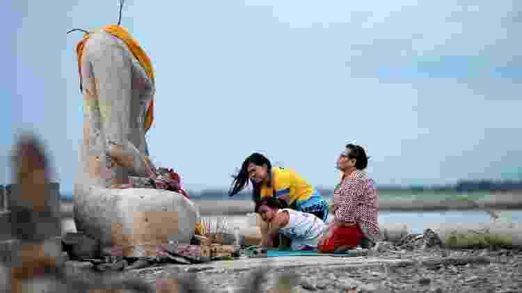 Uma família reza perto das ruínas de uma estátua de Buda sem cabeça, que ressurgiu em uma barragem devido à seca, em Lopburi, Tailândia - Soe Zeya Tun/Reuters