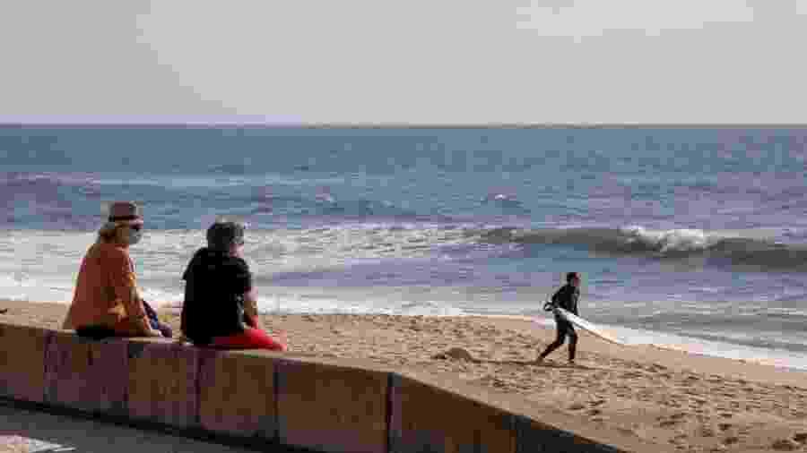 7.mai.2020 - De máscara, pessoas observam o mar em praia de Espinho, em Portugal, atualmente fechada para banhistas - Rita Franca/SOPA Images/LightRocket via Getty Images