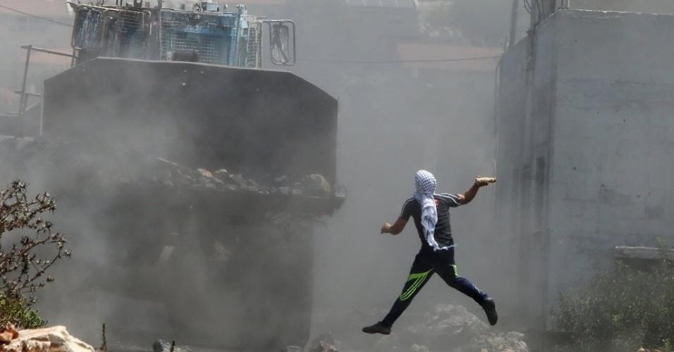 21.ago.2015 - Manifestante palestino joga uma garrafa contra uma escavadeira do Exército israelense, durante manifestação contra a desapropriação de terras palestinas por Israel na aldeia de Kfar Qaddum, perto de Nablus, na Cisjordânia