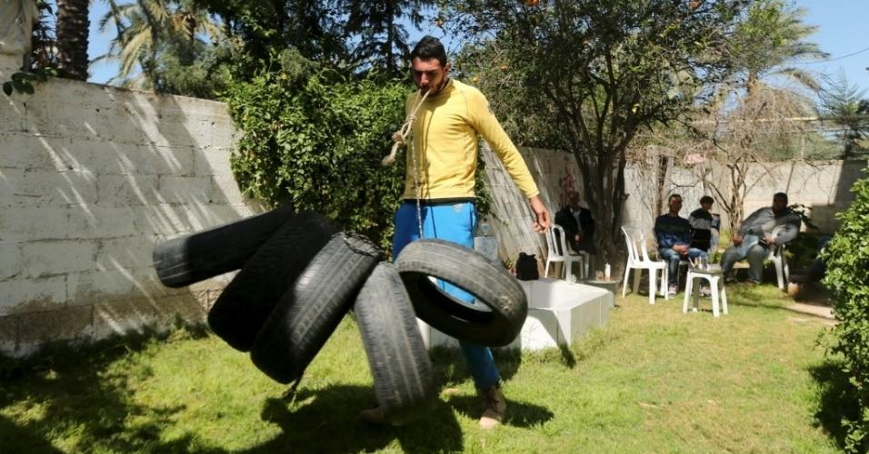 7.mar.2016 - O Sansão de Gaza ganhou fama na região como o homem mais forte da Faixa de Gaza. Ele é tão forte que carrega diversos pneus de caminhão com a boca (como na foto), puxa caminhões com os dentes e resiste a facas caindo sobre sua barriga