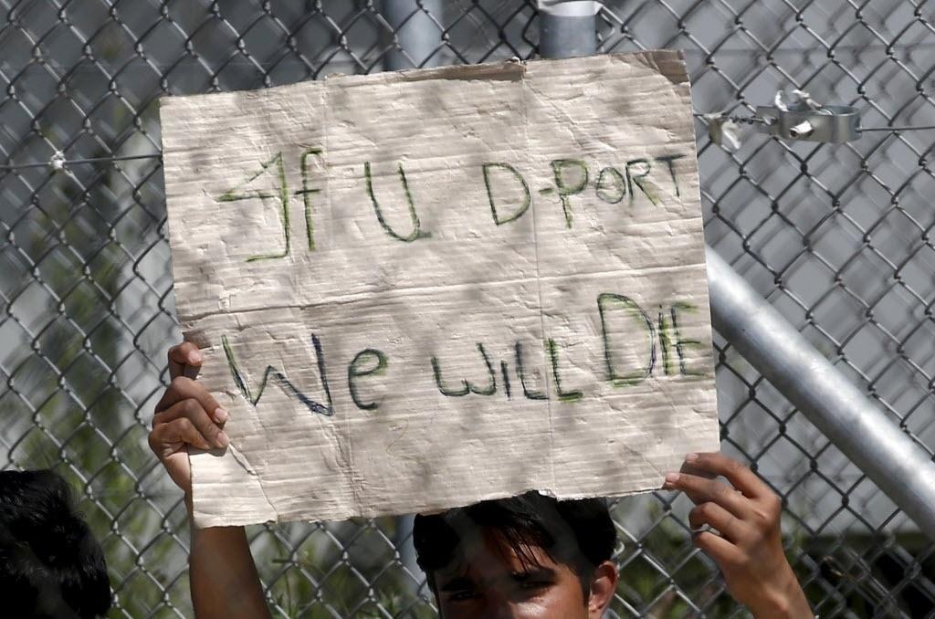5.abr.2016 - Imigrante que será levado à Turquia prende um cartaz com a frase: