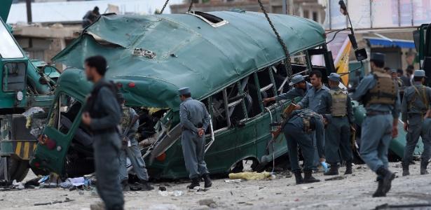 Policiais afegãos observam destroços de ônibus em local de atentado nos arredores de Cabul, no Afeganistão